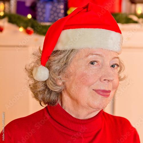 Leinwanddruck Bild Attraktive Großmutter mit Weihnachtsmann-Mütze