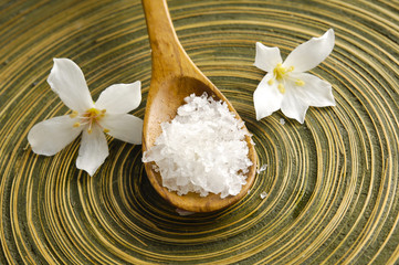 Two frangipani flower and salt in spoon on wooden texture