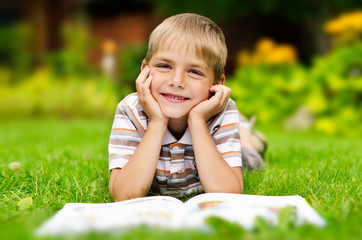 Beauty smiling child boy reading book outdoor on green grass fie