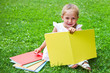 Girl drawing on book on the grass