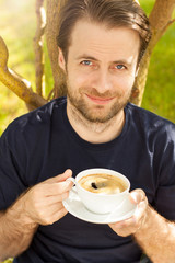 Happy smiling man drinking morning coffee in garden
