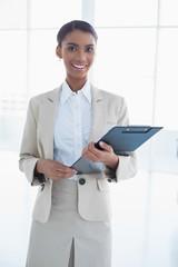 Cheerful elegant businesswoman holding clipboard