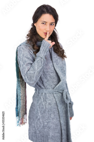 Young model with winter clothes keeping secret