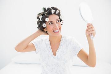 Happy brunette in hair rollers looking in hand mirror