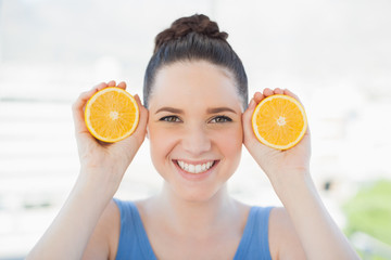 Smiling slender woman in sportswear holding slices of orange