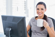 Smiling attractive businesswoman holding mug
