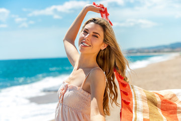 Beautiful girl with scarf on beach.