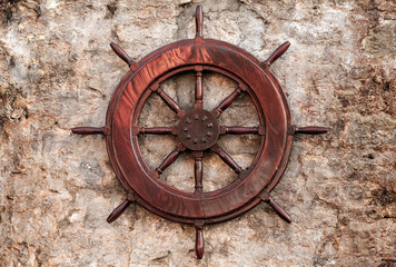 Old wooden ship steering wheel on stone wall