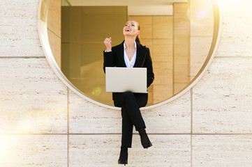 Geschäftfrau mit Laptop freut sich