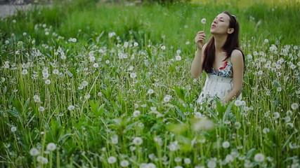 Young Woman Blowing Dandelion and Laughing on a Summer Field