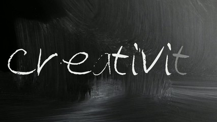 The word Creativity handwritten with white chalk on a blackboard