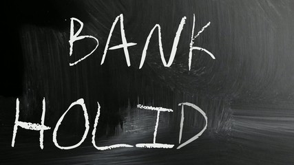 """Bank holiday"" handwritten with white chalk on a blackboard"