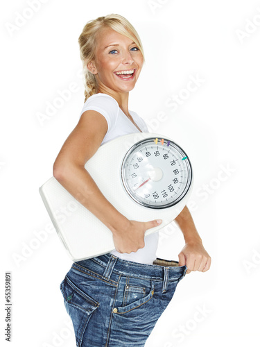 Beautiful girl with scale is proud to lose weight