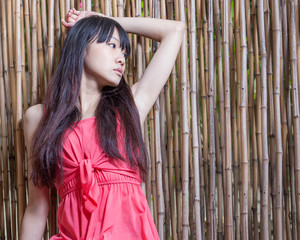 Asian girl by bamboo fence