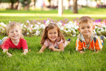 Three happy children lying on the grass