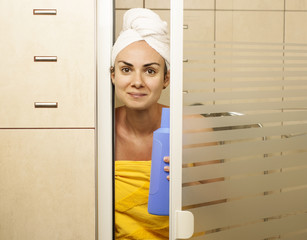 Young woman in the shower cabin with a shower gel