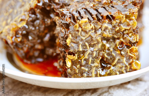Sweet honeycombs with honey on plate, close-up