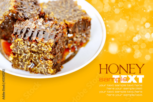 Sweet honeycombs with honey on plate on a yellow background