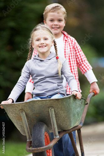 Boy Giving Girl Ride In Wheelbarrow