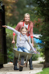 Mother Giving Daughter Ride In Wheelbarrow