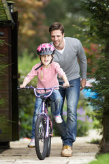 Father Teaching Daughter To Ride Bike In Garden