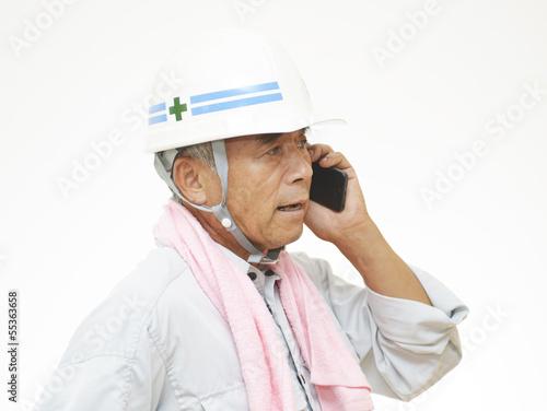 携帯電話で会話をする作業員