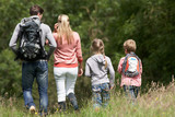 Rear View Of Family Hiking In Countryside