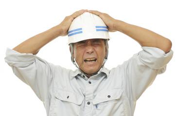 頭を抱える男性作業員