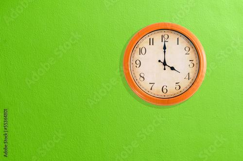 Leinwanddruck Bild Clock showing 4 o'clock on a green wall