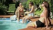Three female friends sunbathing and chatting by the pool