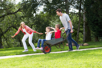 Parents Giving Children Ride In Wheelbarrow