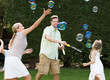 Family Playing With Bubbles In Garden