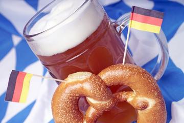 Maßkrug mit Weißbier und Brezel auf einer bayerischen Fahne