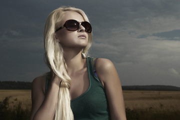 Beautiful blond woman on the field.raining.sunglasses