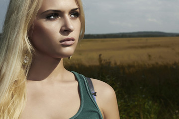 Beautiful blond young woman on the field.nature background