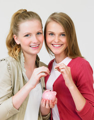 Two Teenage Girls Putting Money Into Piggy Bank