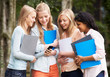 Group Of Female Teenage Students With Mobile Phone Outdoors