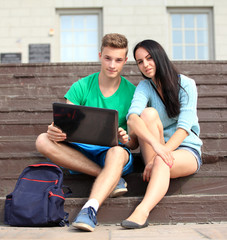 Two students studying with computer notebook outdoors