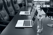 Empty conference room with laptops on table in shades of grey