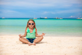 Beautiful little girl sitting in a lotus position on an exotic poster
