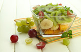 Tasty fruit salad in glass bowl, on white wooden table