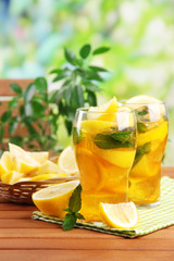 Iced tea with lemon and mint on wooden table, outdoors