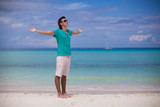 Young man spread his arms standing on white sandy beach
