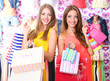 Two beautiful young woman in shop with shopping bags