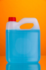 Blue liquid for car in canister on orange background