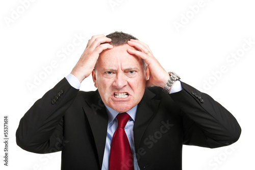Angry businessman with hands in his head isolated on white