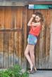 девушка стоящая около деревянной стены