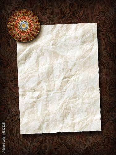 Paper sheet with paperweight on wooden background texture.