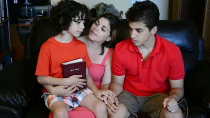 Family Discussing the Bible and Praying