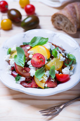 salad with red, yellow and black tomatoes and feta cheese